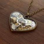 Širdelės formos pakabukas su laikrodžių detalėmis